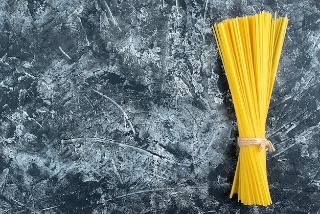 Bovenaanzicht rauwe lange pasta op grijze achtergrond keuken pasta deeg keuken kleur voedsel koken keuken vrije ruimte