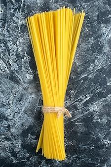 Bovenaanzicht rauwe lange pasta op grijze achtergrond keuken pasta deeg keuken kleur voedsel koken keuken