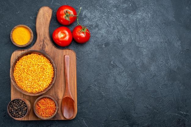 Bovenaanzicht rauwe linzen met kruiden en verse rode tomaten op donkere ruimte