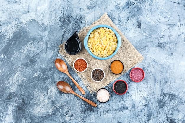 Bovenaanzicht rauwe pasta in kom met kruiden, lepel, houten lepels op gips en stuk zak achtergrond. horizontaal