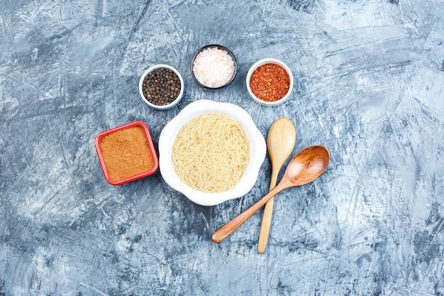 Bovenaanzicht rauwe pasta in witte plaat met kruiden, houten lepels op grijze gips achtergrond. horizontaal