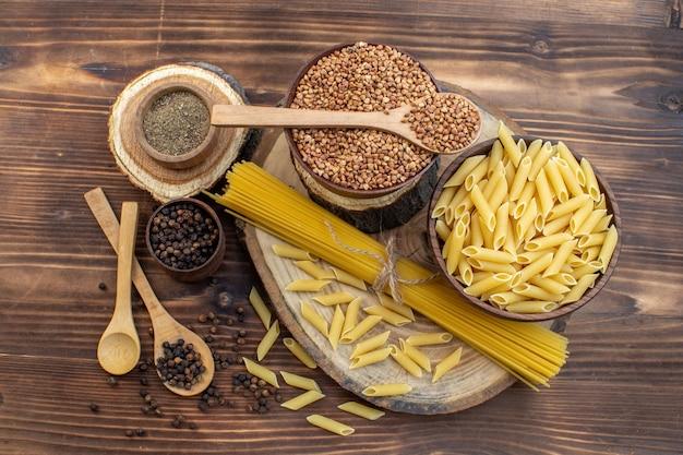 Bovenaanzicht rauwe pasta met boekweit en kruiden op bruine ondergrond