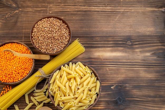 Bovenaanzicht rauwe pasta met boekweit en linzen op bruin oppervlak