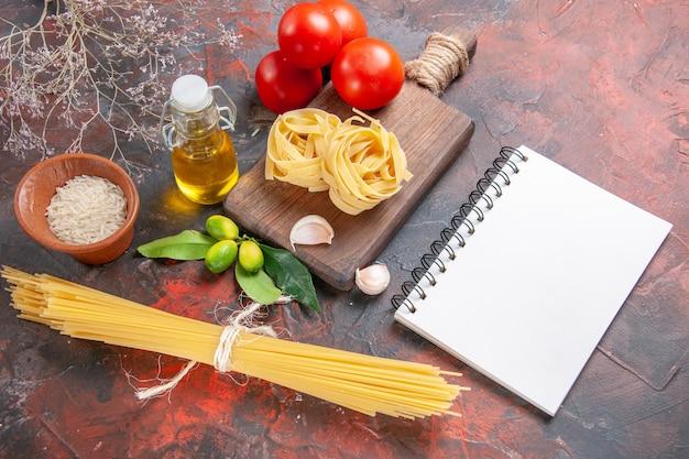 Bovenaanzicht rauwe pasta met olietomaten en knoflook op donker bureau rauw pastadeeg