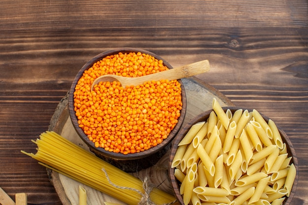 Bovenaanzicht rauwe pasta met oranje linzen op bruin oppervlak