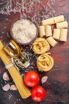 Bovenaanzicht rauwe pasta met rijst en tomaten op de donkere ondergrond deeg pasta rauw
