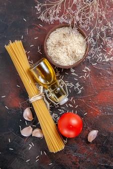 Bovenaanzicht rauwe pasta met verschillende ingrediënten op donkere kleur pastadeeg