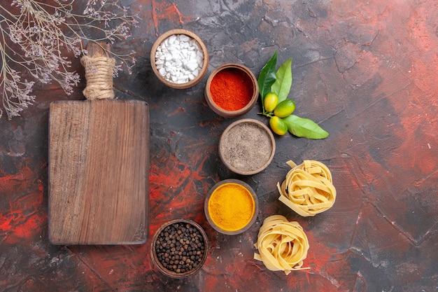 Bovenaanzicht rauwe pasta verschillende kruiden op donkere oppervlak rauwe deeg pasta