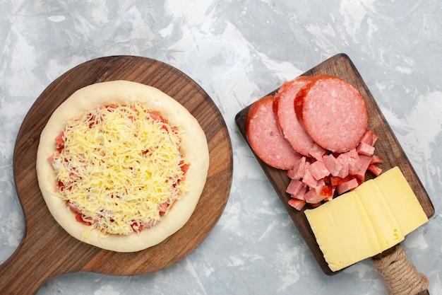 Bovenaanzicht rauwe pizza met kaas en worst op licht wit