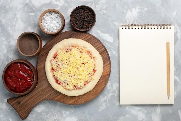 Bovenaanzicht rauwe pizza met kaaskruiden op wit