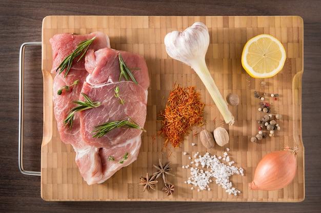 Bovenaanzicht rauwe pork chop steak en knoflook, peper op houten achtergrond.