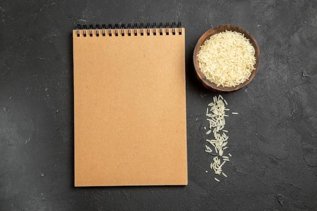 Bovenaanzicht rauwe rijst met notitieblok op donkere oppervlakte maaltijd eten rijst rauw