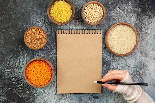 Bovenaanzicht rauwe rijst met vermicelli en rauwe boekweit in kleine potjes op de lichtgrijze tafel