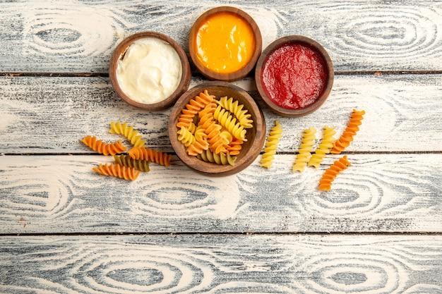 Bovenaanzicht rauwe spiraalvormige pasta met verschillende kruiden op grijs