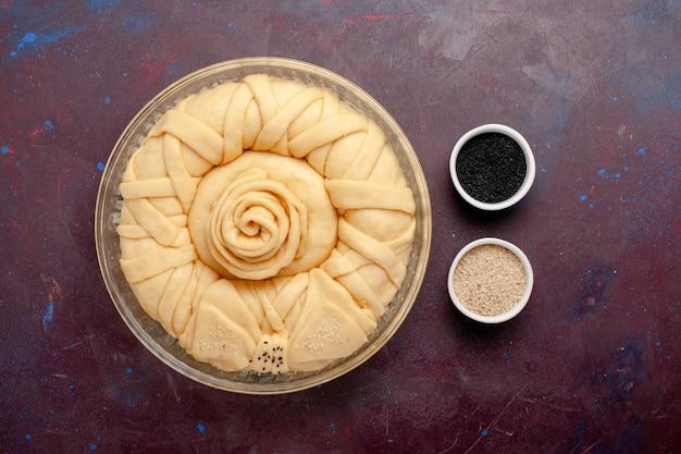 Bovenaanzicht rauwe taartdeeg ronde gevormd op donkerpaars bureau