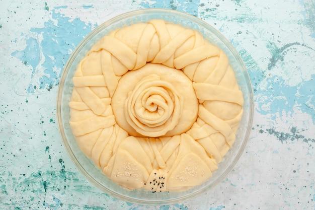 Bovenaanzicht rauwe taartdeeg ronde gevormd op het blauwe oppervlak