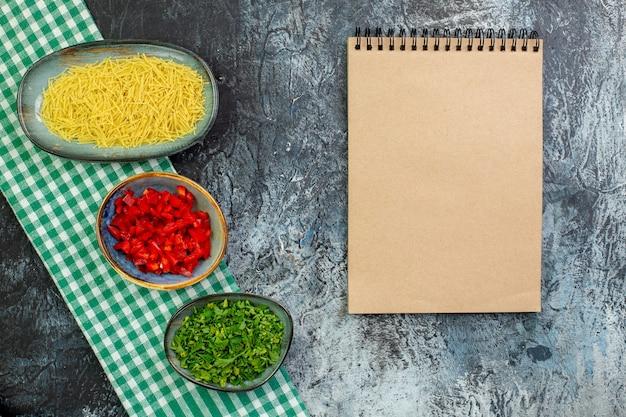 Bovenaanzicht rauwe vermicelli met greens en gesneden paprika op grijze tafel