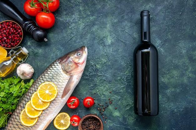 Bovenaanzicht rauwe vis pepermolen wijnfles op tafel