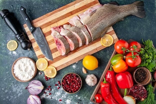Bovenaanzicht rauwe vis plakjes mes op snijplank groenten op houten serveerplank pepermolen op keukentafel