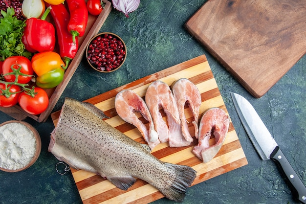 Bovenaanzicht rauwe vis plakjes op snijplank groenten op houten serveerplank mes op keukentafel