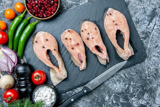 Bovenaanzicht rauwe vis plakjes op zwarte bord mes groenten op grijze achtergrond