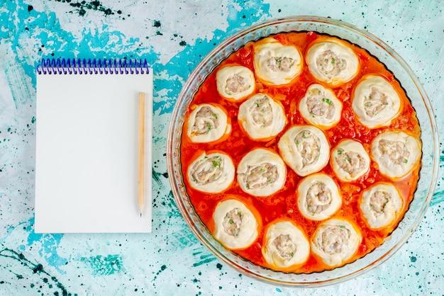 Bovenaanzicht rauwe vlezige deeg deegplakken met gehakt binnen met tomatensaus in glazen pan met blocnote op het blauwe bureau eten maaltijd deeg vlees diner