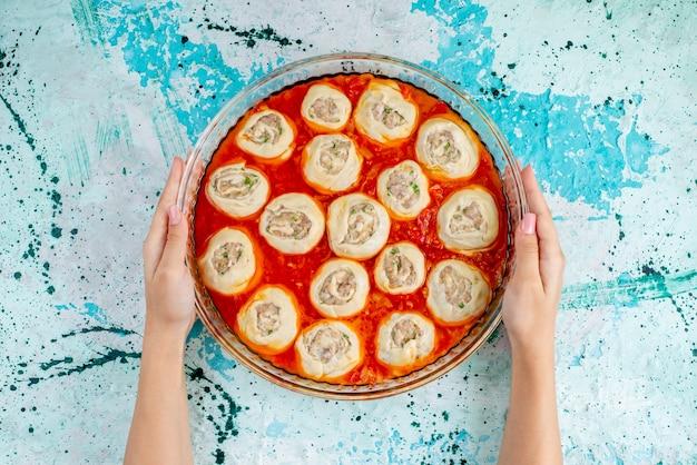 Bovenaanzicht rauwe vlezige deeg plakjes met gehakt vlees met tomatensaus in glazen pan in de oven op het blauwe bureau eten maaltijd deeg vlees diner