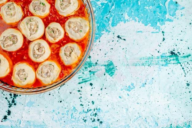Bovenaanzicht rauwe vlezige deegplakken met gehakt met tomatensaus in glazen pan op het blauwe bureau eten maaltijd deeg vlees diner