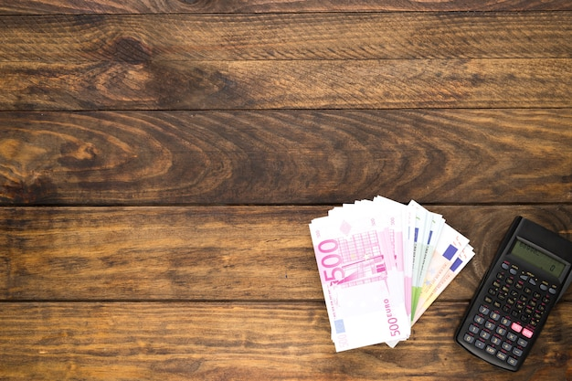 Bovenaanzicht regeling met bankbiljetten en zakrekenmachine
