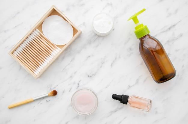 Bovenaanzicht regeling met cosmetica op marmeren tafel