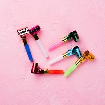 Bovenaanzicht regeling met fluitjes en roze achtergrond