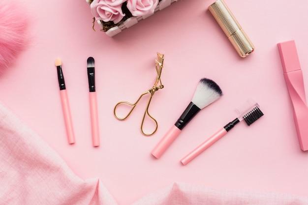 Bovenaanzicht regeling met make-up borstels op roze achtergrond