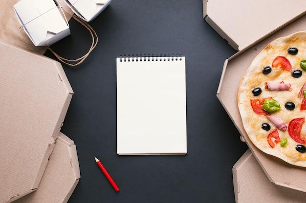 Bovenaanzicht regeling met pizzadozen en notitieboekje