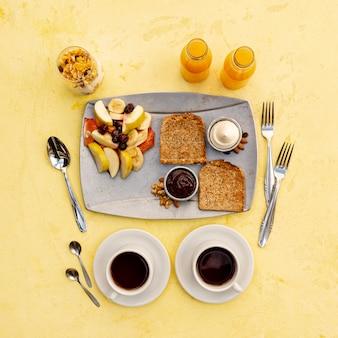 Bovenaanzicht regeling met smakelijk ontbijt en gele achtergrond