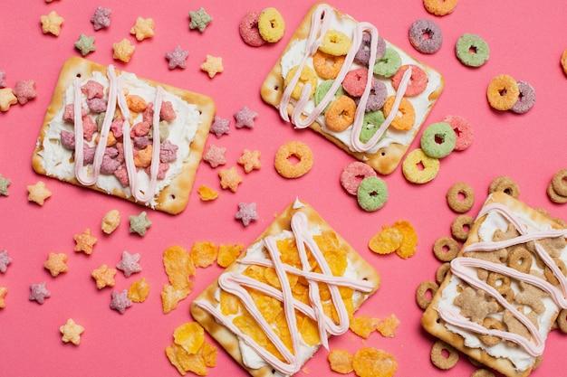 Bovenaanzicht regeling met taartjes op roze achtergrond