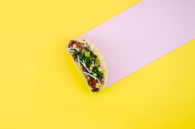 Bovenaanzicht regeling met taco op gele achtergrond