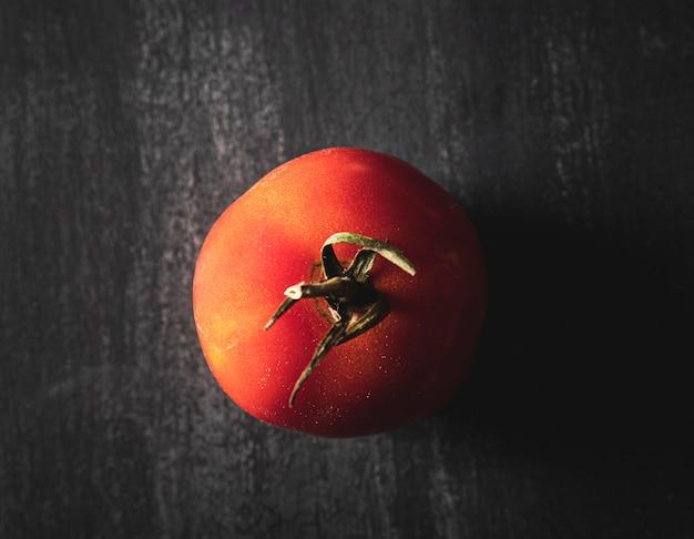 Bovenaanzicht regeling met tomaat op zwarte achtergrond