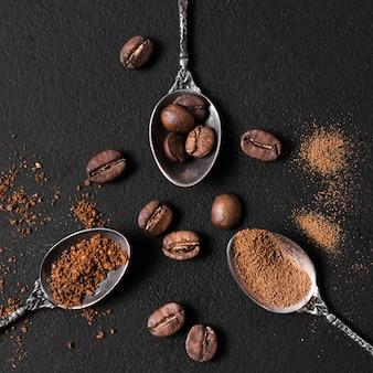 Bovenaanzicht regeling van lepels gevuld met geroosterde koffiebonen en poeder