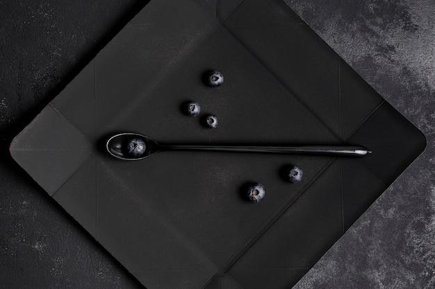 Bovenaanzicht regeling van zwarte bonen op donkere plaat
