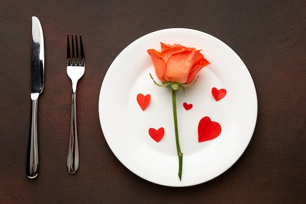 Bovenaanzicht regeling voor valentijnsdag diner met oranje roos