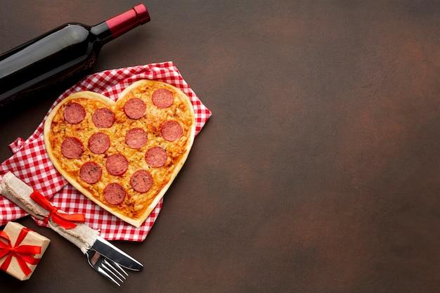 Bovenaanzicht regeling voor valentijnsdag met hartvormige pizza en kopie ruimte