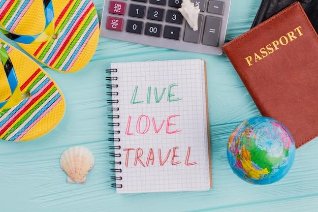 Bovenaanzicht reisconcept met paspoort, sandaal, zeeschelp op blauwe achtergrond. leef liefdesreizen op het blocnote.