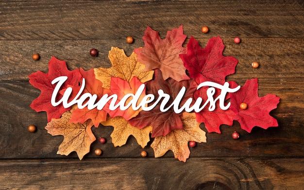 Bovenaanzicht reislust belettering met bladeren