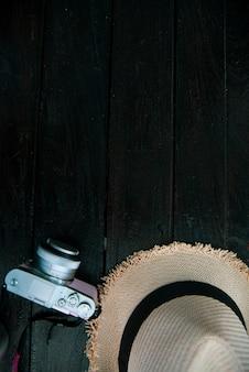 Bovenaanzicht reizen concept met camera en hoed op tafel
