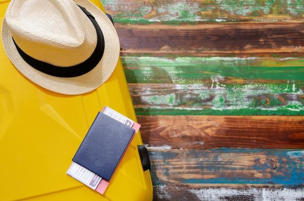 Bovenaanzicht reizigersaccessoires van gele bagage, blauw paspoort en zonnehoed op verweerd houten oppervlak
