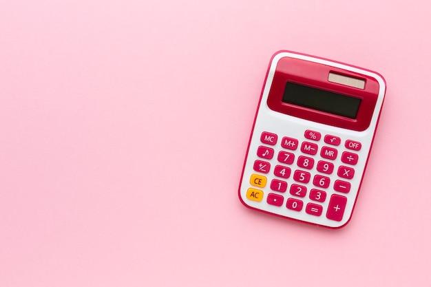 Bovenaanzicht rekenmachine op roze achtergrond