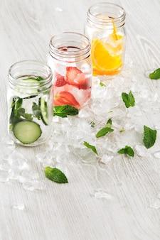 Bovenaanzicht rij rustieke potten in gecrashte ijsblokjes met sinaasappel, aardbei, komkommer en munt bereid om verse zelfgemaakte limonade te maken met bruisend water.