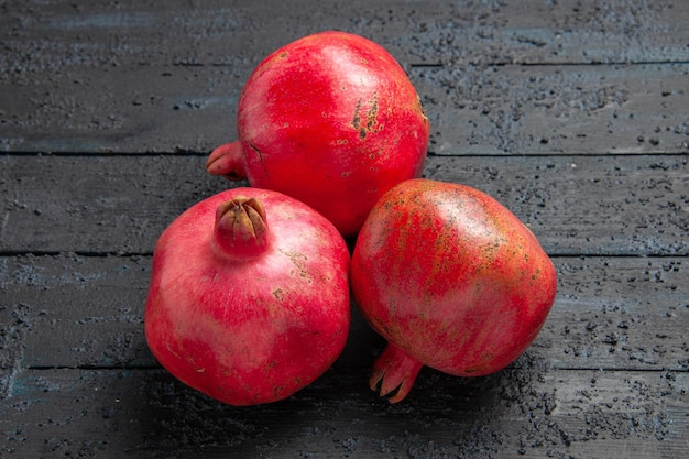Bovenaanzicht rijpe granaatappels drie rijpe granaatappels op donkere ondergrond