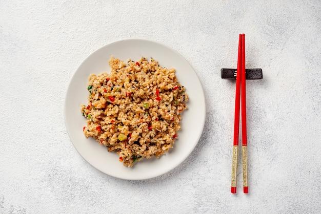 Bovenaanzicht rijst met groenten op plaat en eetstokjes