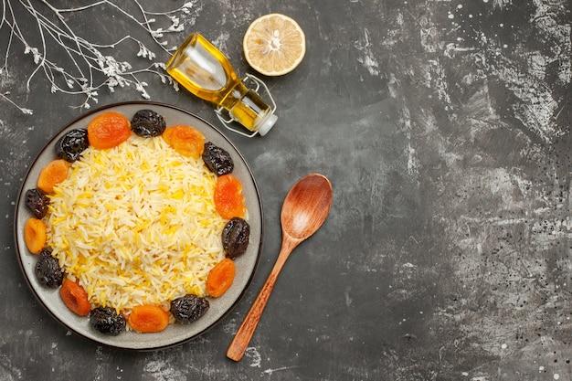 Bovenaanzicht rijst plaat van rijst met gedroogde vruchten citroen lepel fles olie